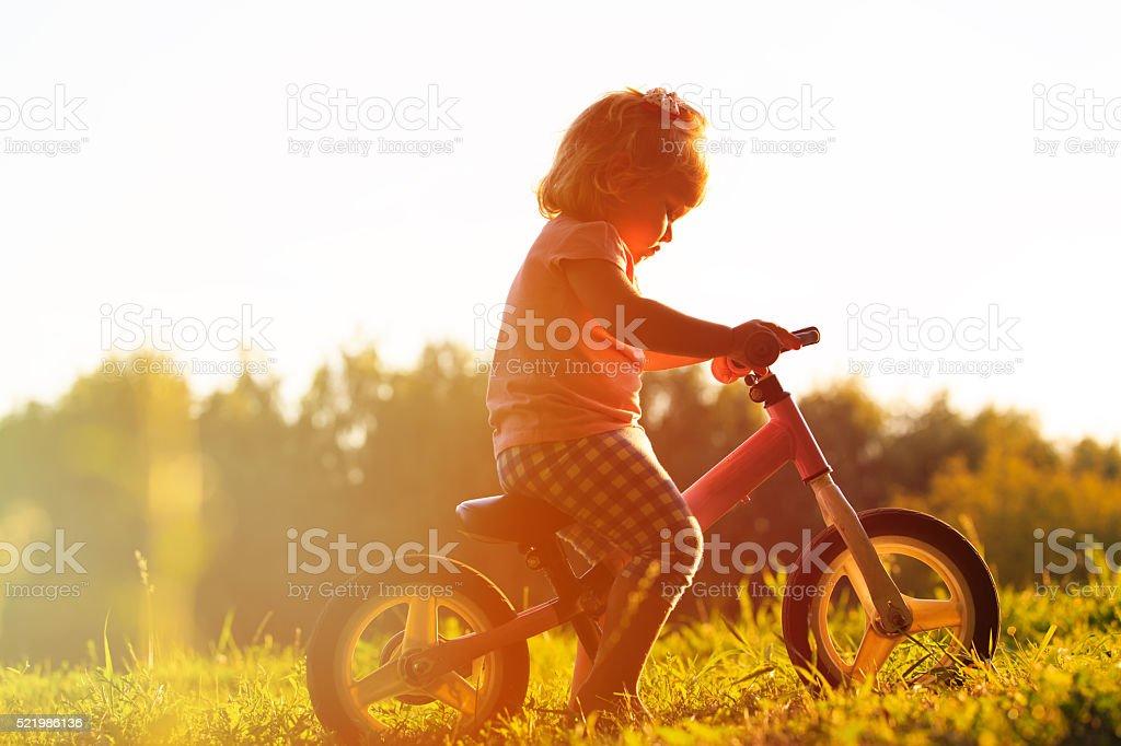 little girl riding bike at sunset, active kids stock photo