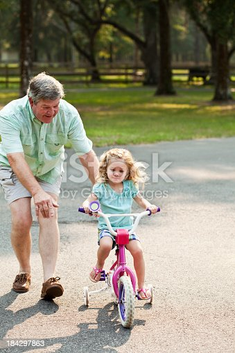 853720192 istock photo Little girl riding bike with grandfather 184297863