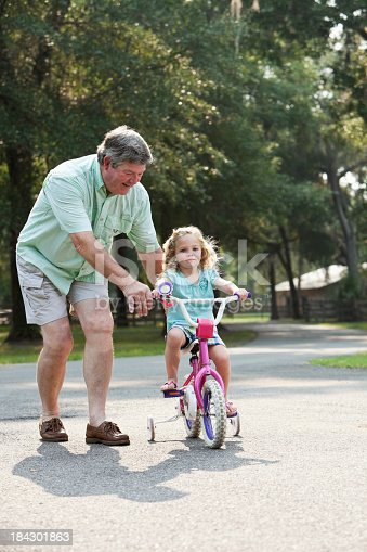 853720192 istock photo Little girl riding bike with grandfather 184301863