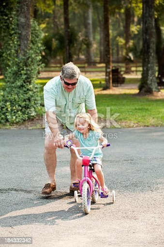 853720192 istock photo Little girl riding bike with grandfather 184332342