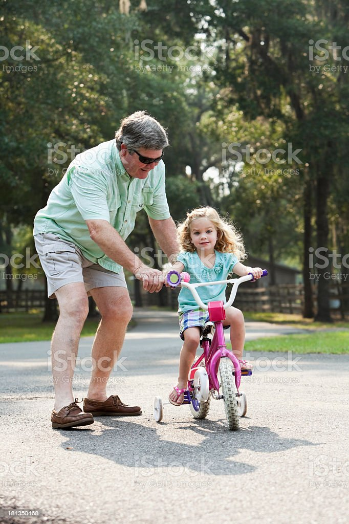 Little girl riding bike with grandfather royalty-free stock photo
