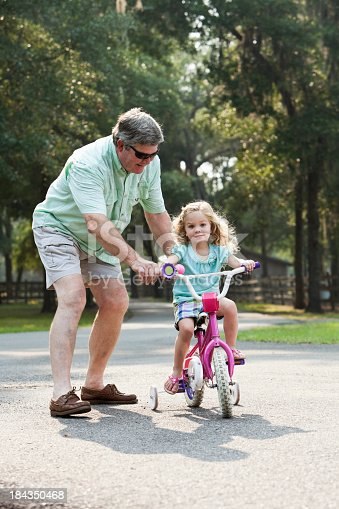 853720192 istock photo Little girl riding bike with grandfather 184350468