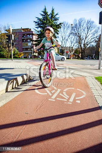 Little girl Riding Her Bicycle in the City