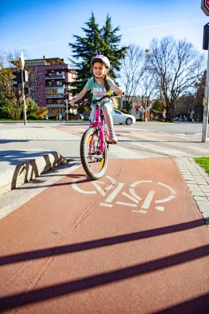 kleines mädchen fährt fahrrad in der stadt - fahrradwege stock-fotos und bilder