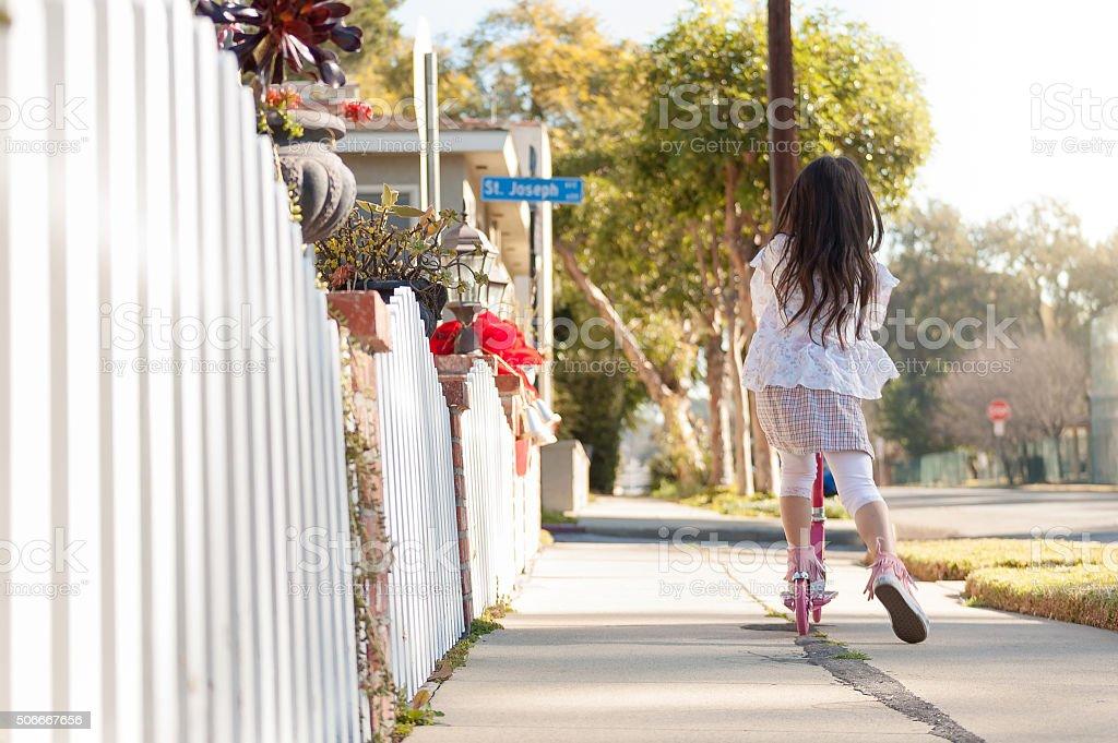 Menina andando de moto ao longo da calçada seu - foto de acervo
