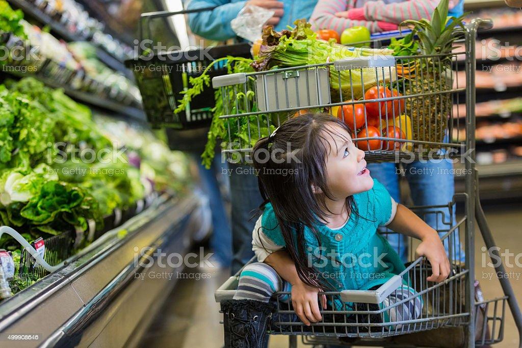 Bambina di stare in fondo carrello di supermercato shopping carrello - foto stock