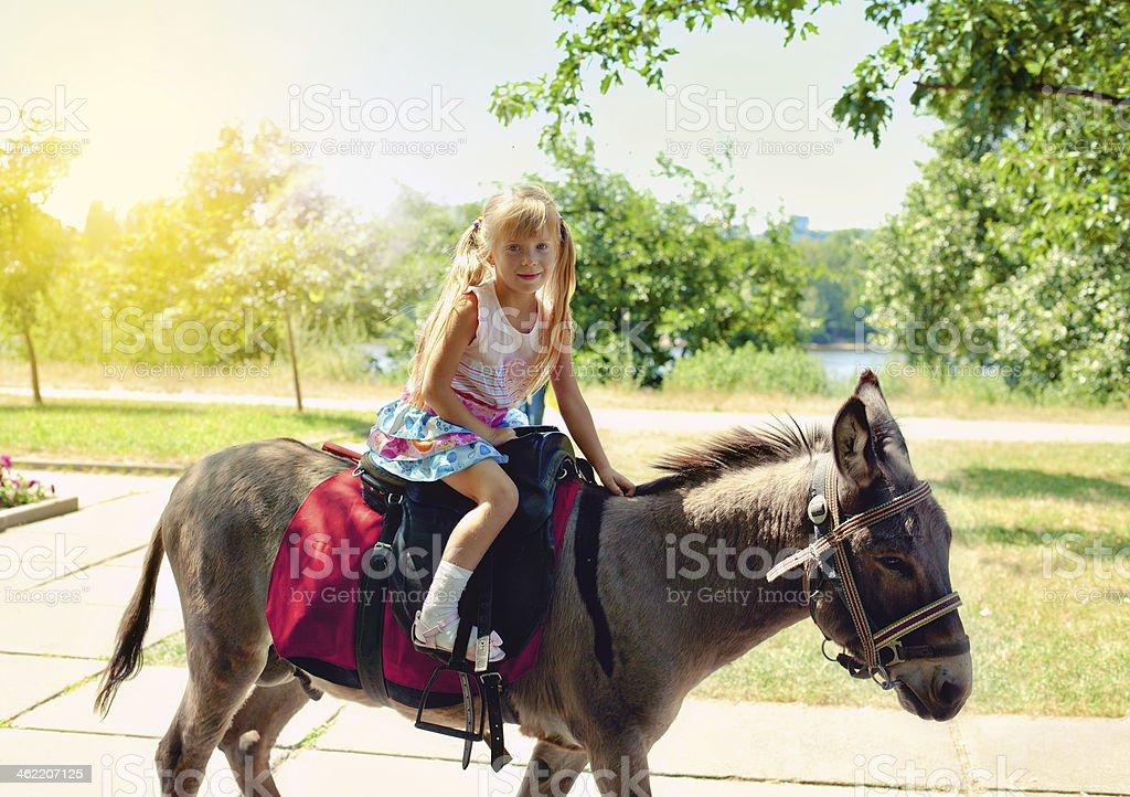 Kleines Mädchen Reiten auf einen Esel – Foto
