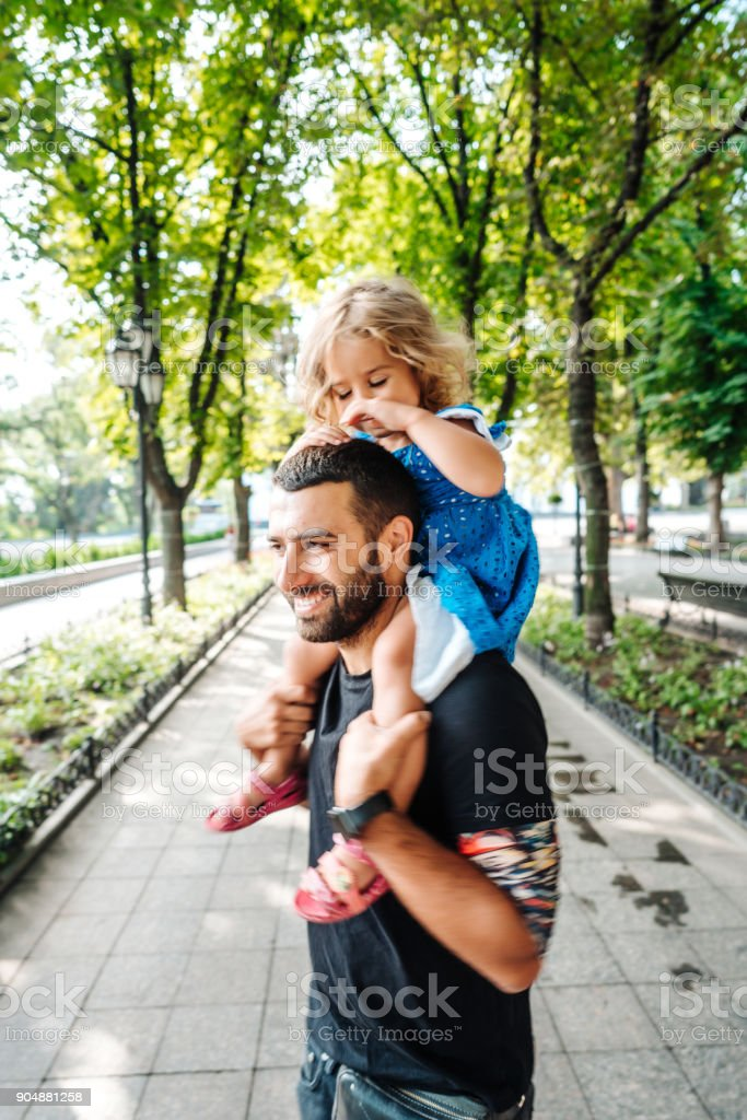 little girl riding on dads neck stock photo