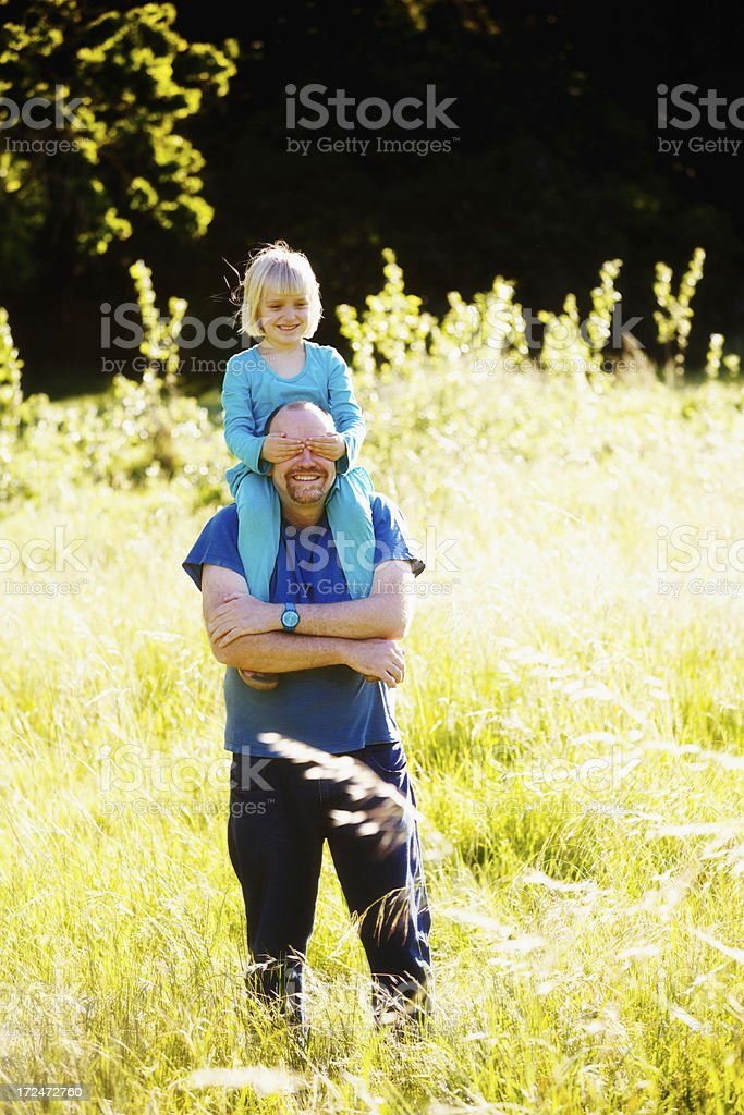 Little girl riding on happy dad's shoulders blindfolds him, teasing stock photo