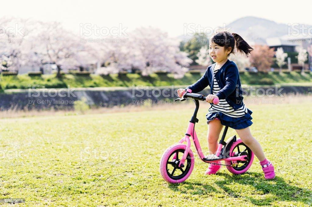 Petite fille équitation runbike en plein air. photo libre de droits