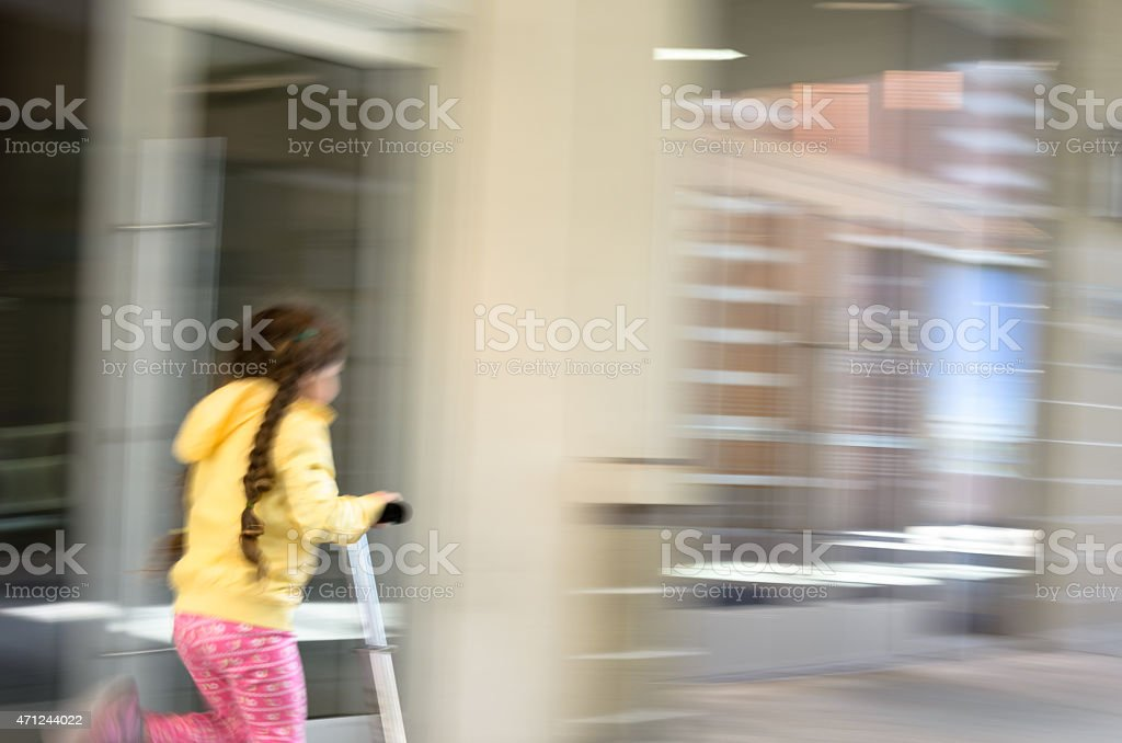 Little girl riding scooter motion blur stock photo