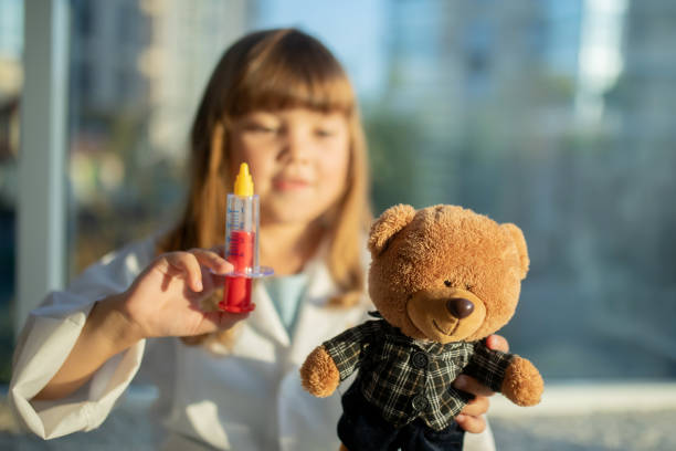 RUSSIA, KRASNODAR - SEPTEMBER 7 2019: Little girl role-playing a doctor or nurse holding a giant syringe stock photo