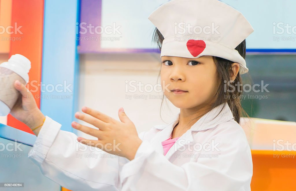 Little girl roll playing as a Doctor stock photo