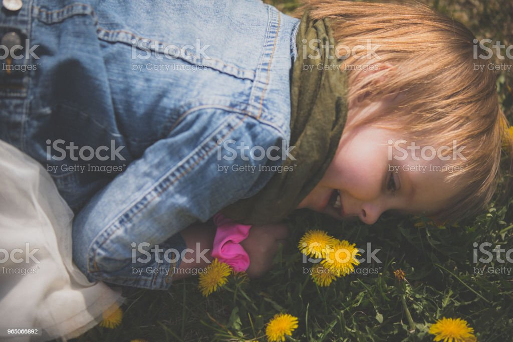 Little girl rolling and playing in the flowers zbiór zdjęć royalty-free