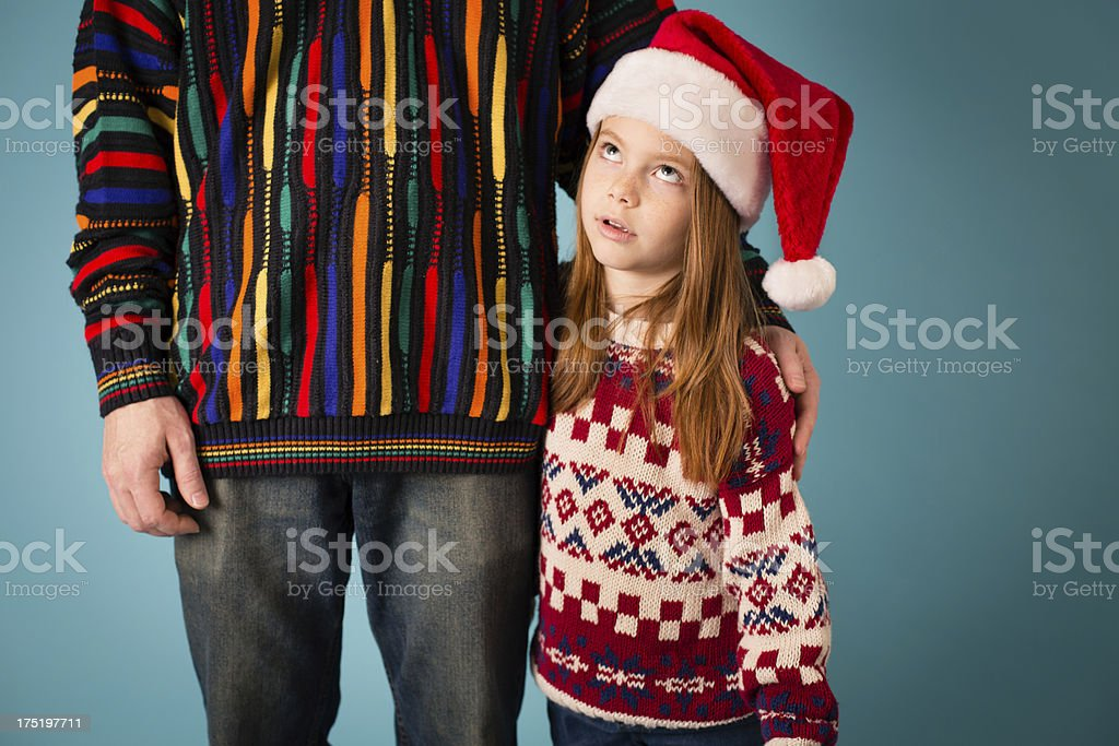 Little Girl Rolling Eyes at Dad, Both Wearing Ugly Sweaters stock photo