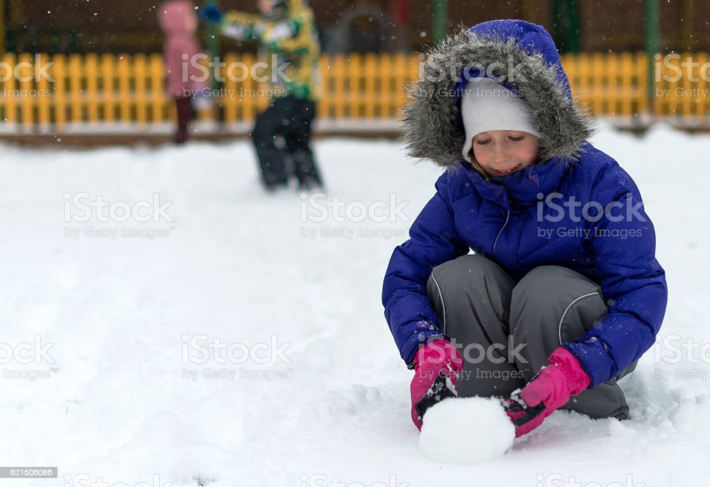 Little girl rolling snowball in winter. Lizenzfreies stock-foto
