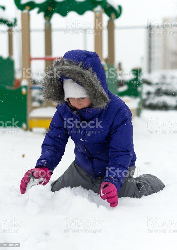 Little girl rolling snowball in winter. photo libre de droits