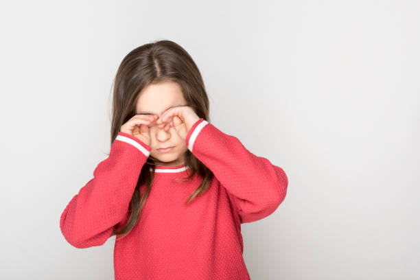Little girl rubbed her eyes stock photo