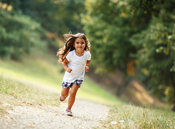 Little girl run through the park. stock photo