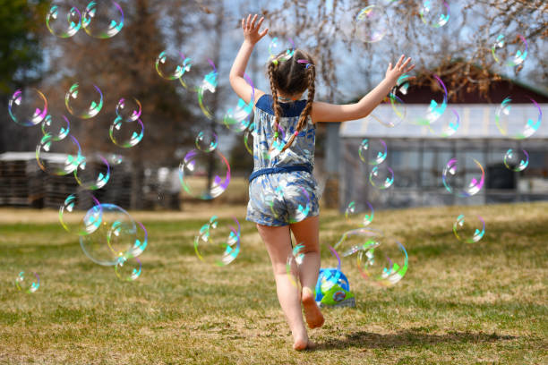 Little girl running after bubbles stock photo