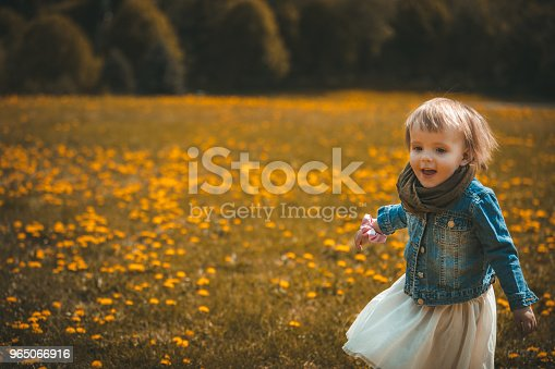 Little girl running and playing in the flowers