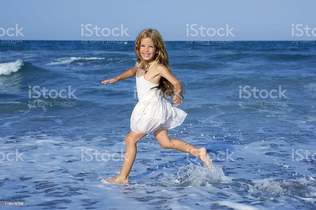 Little girl running beach in blue sea royalty-free stock photo