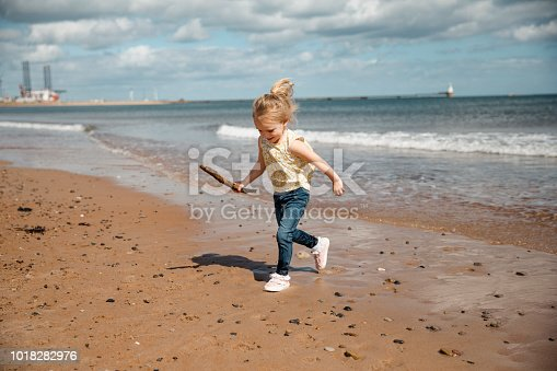A shot of a little girl running across the beach whilst smiling and holding a wooden stick.