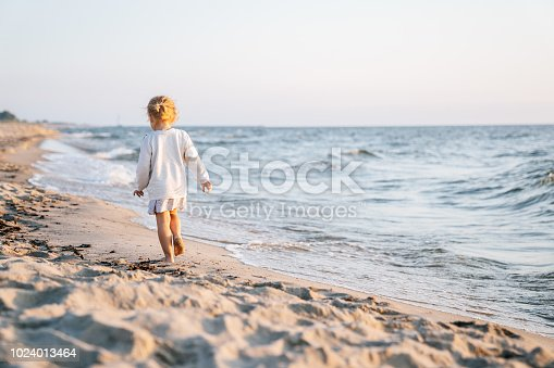 Little girl playing and running on the beach