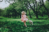 Little cute girl in a pink dress running on the grass. Back view.