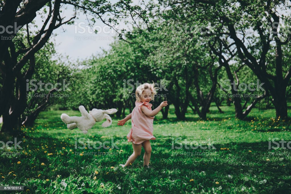 Little girl running on the grass. stock photo