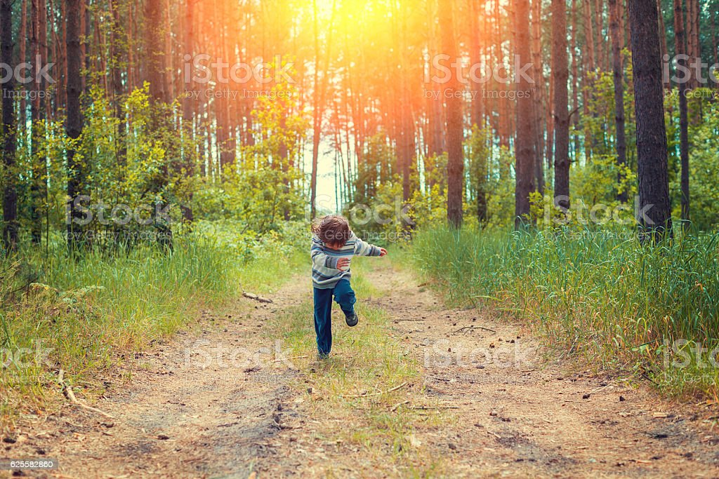 Little girl running on the dirt rural road in the pine forest