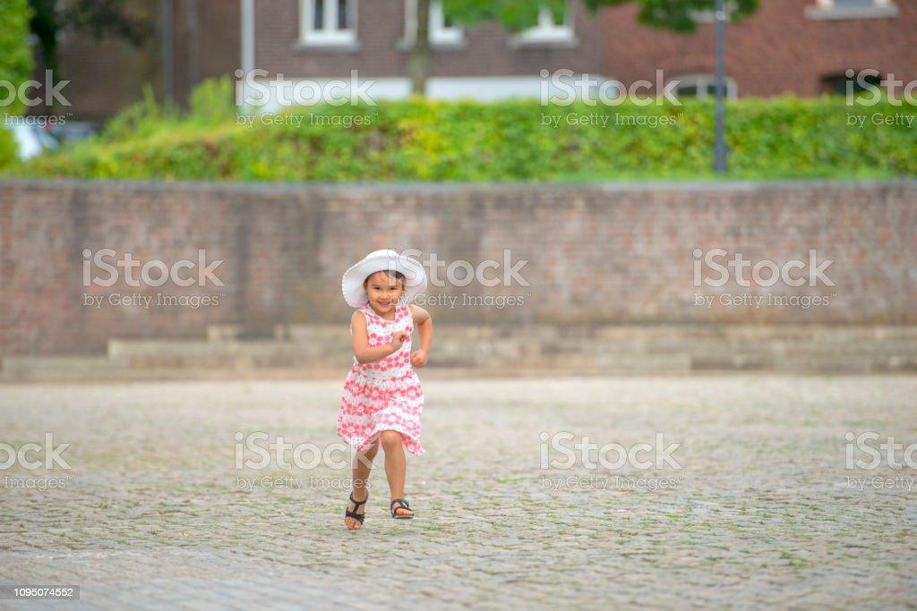 Petite fille en cours d'exécution dans la rue en ville - Photo