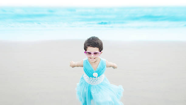 Little girl running & playing at  blue beach stock photo
