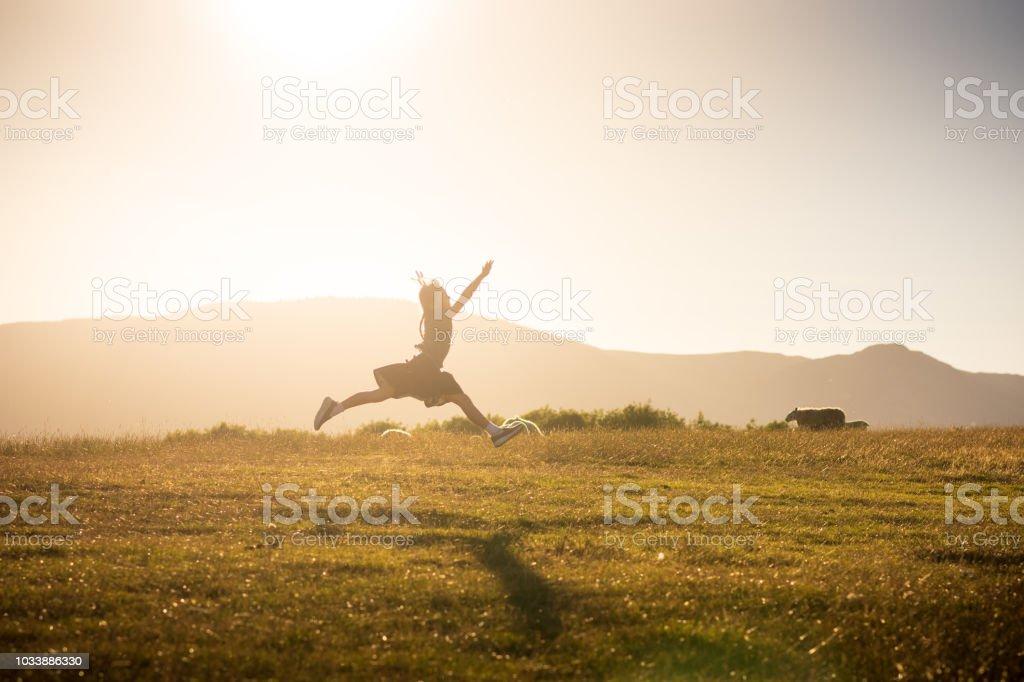 Little girl running through the rural sunset pastures of Keswick, England stock photo