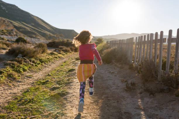 Kleines Mädchen, das durch die spanische Landschaft läuft, Rambla del Playazo, Cabo de Gata-Naturpark Nijar, Spanien – Foto