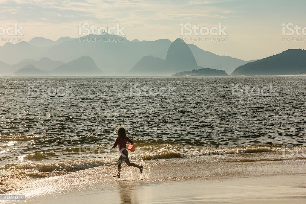 Little Girl Running Towards Sea Sugar Loaf in Background stock photo