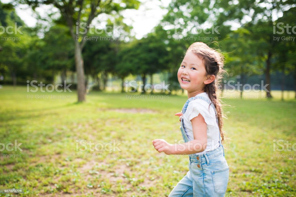 Little girl running while laughing stock photo