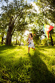 Active little girl running while holding a kite at garden. Vertical Shot. Slight motion blur due to running.