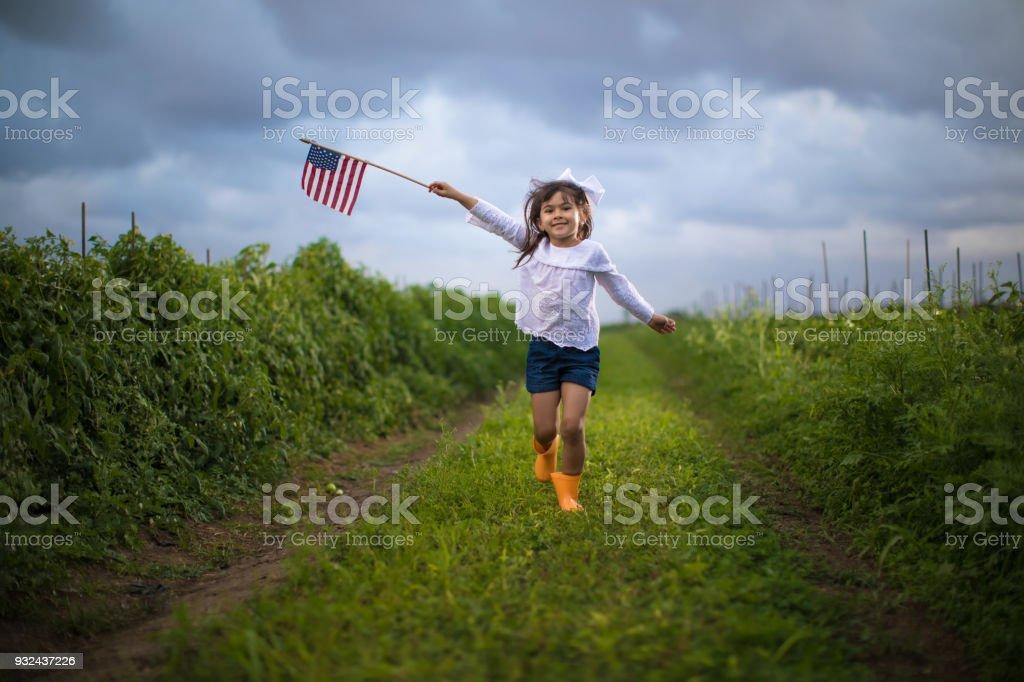 Niña corriendo con una bandera americana - foto de stock