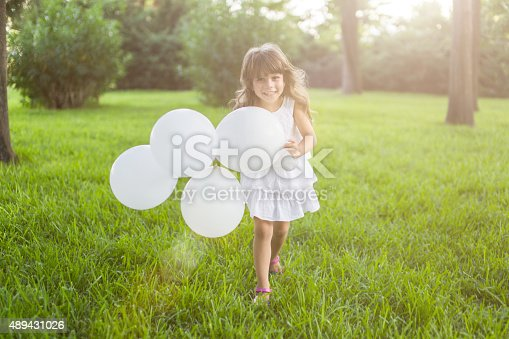 istock Little girl running with white balloons in the park 489431026