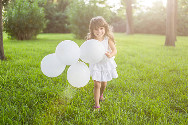 Kleines Mädchen läuft mit weißen Ballons in den park – Foto