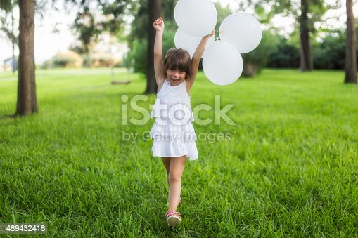 istock Little girl running with white balloons in the park 489432418