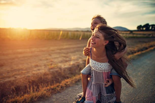 kleines mädchen läuft mit ihrem kleinen bruder - happy trails stock-fotos und bilder