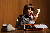 Angry little girl shouting on phone in her office