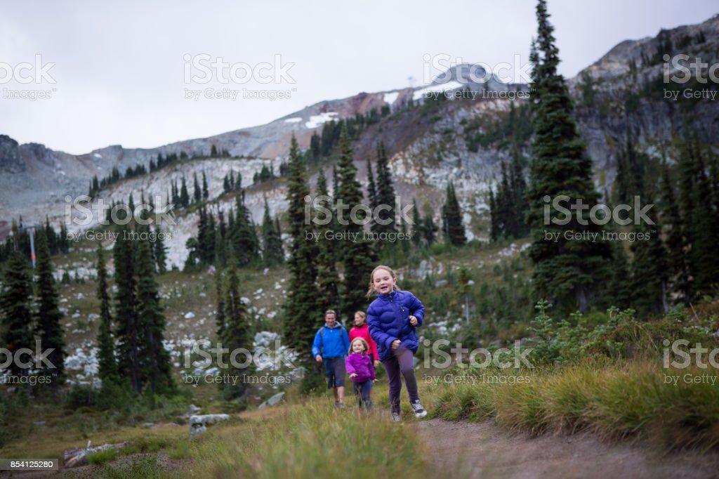 Little girl runs ahead of her family stock photo
