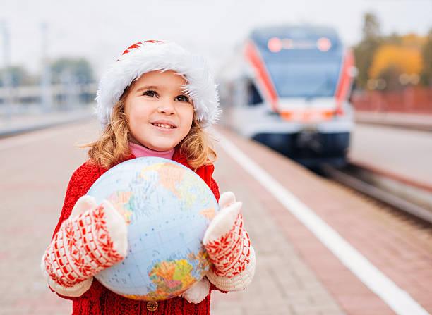 kleines mädchen santa reisen mit einem globus - festzugskleidung stock-fotos und bilder