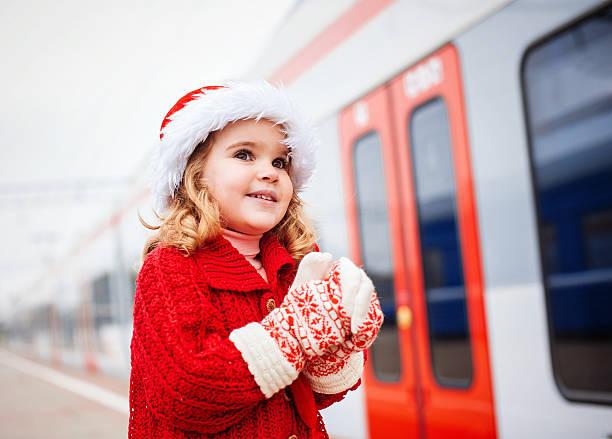 kleines mädchen warten auf einen zug santa - festzugskleidung stock-fotos und bilder