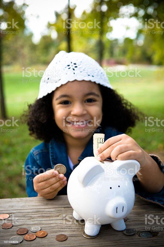 Little Girl Saving Money stock photo