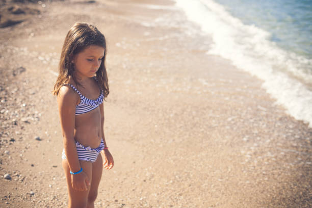 little girl scared of the water - girl alone in swimsuit stock photos and pictures