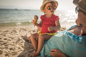 Little girl seating with mother on sandy beach eating icecream